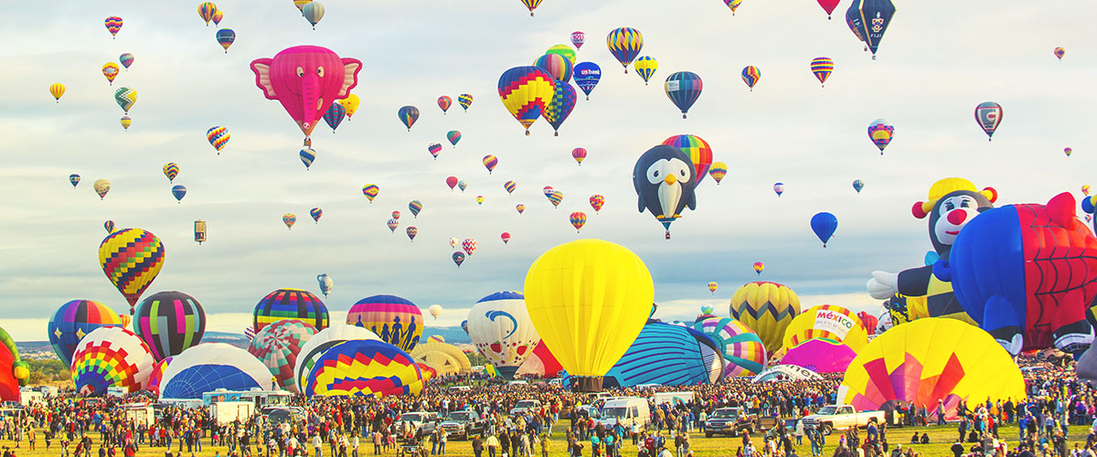 Hot-air balloons taking off in a field.
